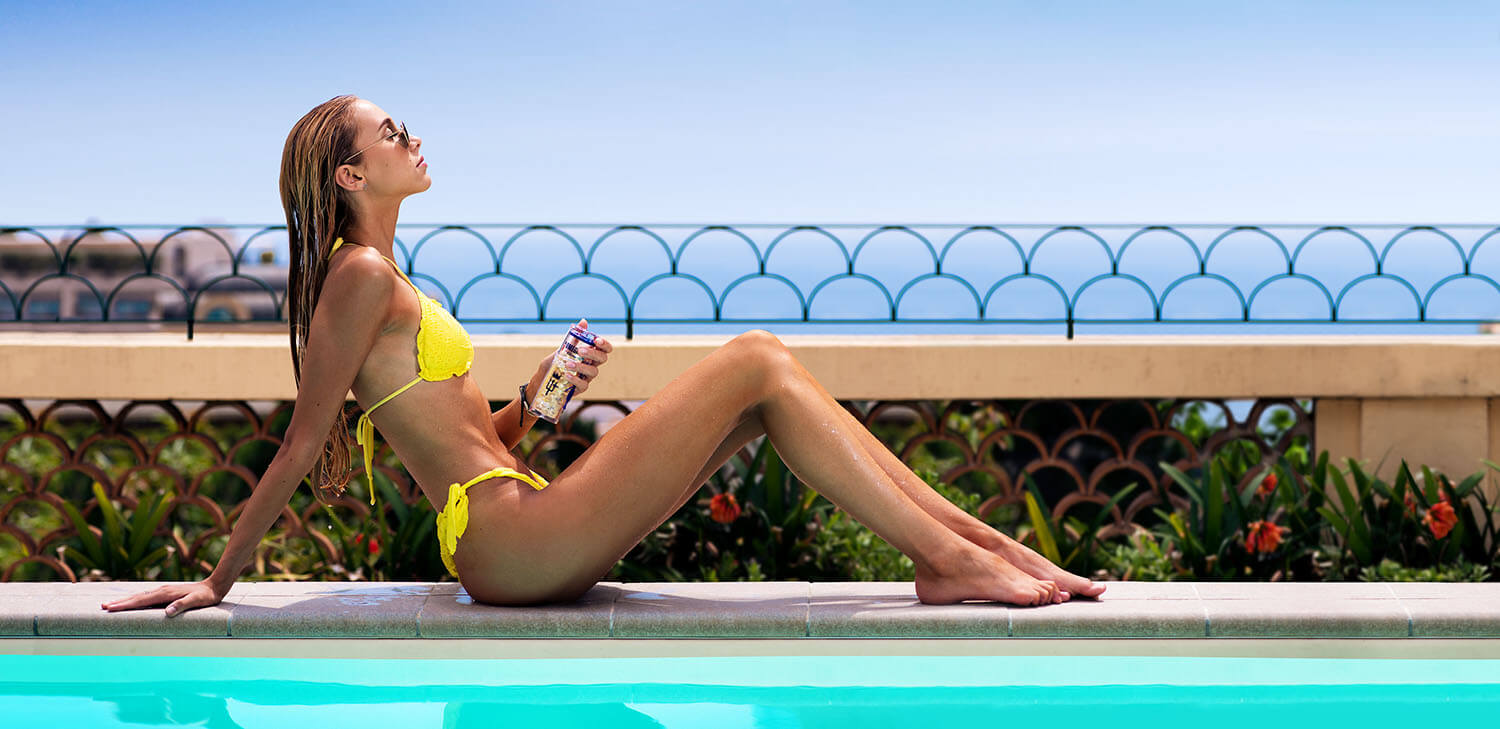 Swiss health & beauty model and Norway Omega ambassador, Lara Holtkamp, at the pool with Omega3 of Norway bottle
